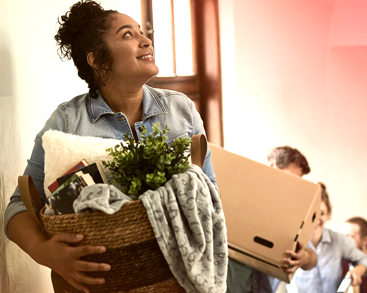 A woman moving into her new home looks happy as she carries a laundry basket full of household items up the stairs