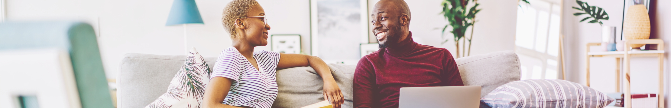 A smiling man sits on the sofa with his wife