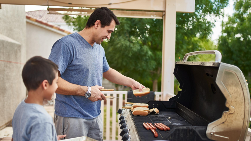 man cooking hot dogs on gas grill
